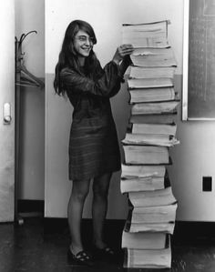 Margaret Hamilton standing next to listings of the actual Apollo Guidance Computer (AGC) source code that guided the USA space craft that went to the Moon.  Click image to learn more about her.