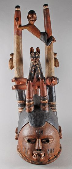 Gelede mask; carved of wood; in the form of human face with two short horns and two long horns, two human figures stretching between long horns, one animal standing on lower human figure with short horn in each front paw, bird? carved on outside of each long horn, human figure standing on back of head with arms reaching behind to grasp base of long horns; hair painted black, animal painted black with white spots, horns painted with black, white and brown stripes.