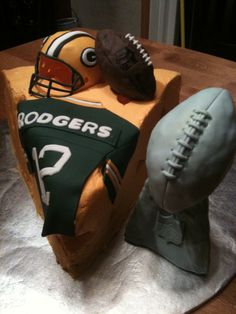 Superbowl XLV Cake - Green Bay Packers - Superbowl XLV cake. 4-layer Cheese head cake covered in buttercream topped with gum paste Green Bay Packer Helmet, fondant covered rice cereal treat NFL football, fondant Aaron Rodgers jersey, and fondant covered rice cereal treat Lombardi trophy.