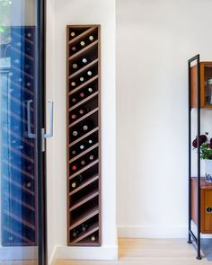 Carefully detailed customwalnut wine rack is slotted discretely into the living room wall