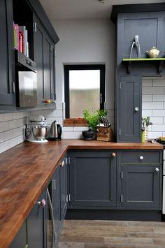 #Muebles de cocina negros, #encimera de madera y paredes blancas.