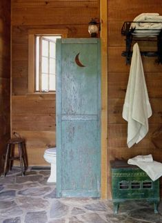 """Outhouse chic  With its stone floor, wide-planked wood walls, and box heater, this bathroom has a definite """"sauna"""" feel to it. The wooden privacy screen between the toilet and the rest of the room is distressed and has a moon-shaped cut-out, just like an outhouse!"""