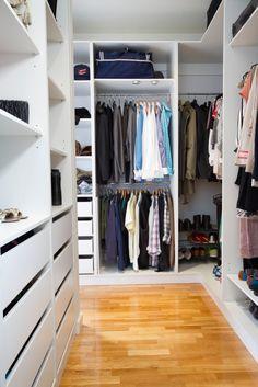 A U-shaped walk-in closet in beautiful multi-toned hardwood floors and white custom storage.