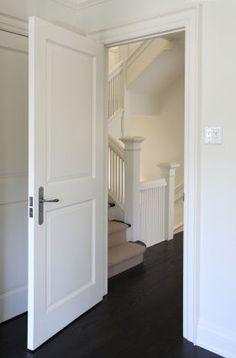 grey walls white trim black door hardware dark floors and chrome