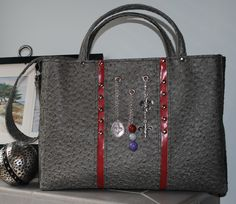 It's Fleur Delicious!  This custom order bag features gray faux ostrich, red pin stripes, nailheads, 3 fleur delis charms and a beaded tassel.  Padded handles and a shoulder strap were also included.  This roomy bag is great for the office or a shopping trip!  Visit me on Facebook at Bobbin My Thread to see more designs by Nena!
