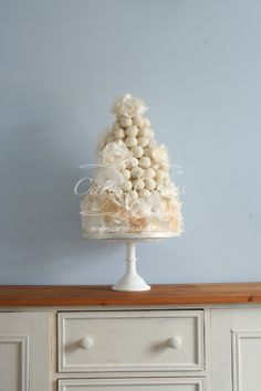 Cake pop tower, with an additional cake underneath and decorated with wafer flowers which have small edible silver leaf details