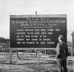"""British serviceman reads a sign at Bergen-Belsen concentration camp, May 1945 German New Order in Europe - a correlation to """"The New World Order"""" trying to put all people under one King?"""