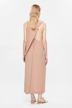 This long dress is made from pure silk with grosgrain strap details along the back. A layered design that softly drapes diagonally across the back, it is completed with front slit and a hidden press stud and zip-up fastening.