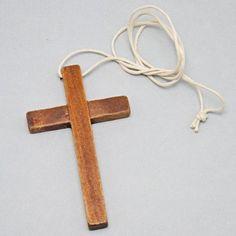 Croce in legno scuro con cordino in bianco da indosaare sulla tunichetta. La croce è alta 10 cm ed è larga 6 cm. Made in Italy.