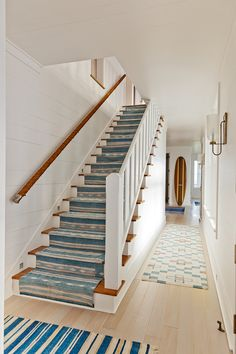"Leading to the lower level, this staircase fully embraces a coastal feel with rope railing and a vintage stair runner. Floors are 6"" White Oak with a White washed finish.  Stair runners were cut up old Striped Dhurrie rugs.  The rope railing is made by a local craftsman.  Sconces: Urban Electric."