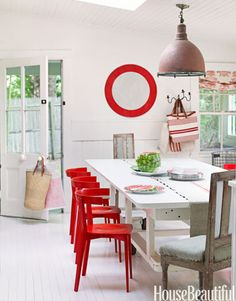 "Because her house in Bridgehampton, New York, ""meanders around corners and up and down steps,"" design consultant Ellen O'Neill couldn't make sense of the flow. So she painted everything Benjamin Moore's Linen White: ""It's the blank-canvas approach."" A vintage English road sign gives the dining room a focal point. Red chairs from Design Within Reach. Curtain fabric by Les Indiennes."