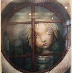 Niño triste tras la ventana