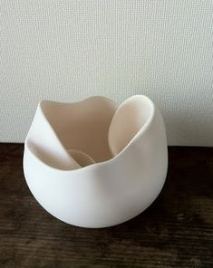 Japanese ceramics artist Tomaru Atsuko creates white objects made out of a mix of ceramic and porcelain that recall snail shells, half-opened roses and folded handkerchiefs.
