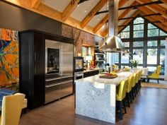 This ski lodge kitchen has wood flooring, a wrap-around marble center island, patterned wall cover, gabled rood with exposed beams and a wall of glass that opens to the outside.