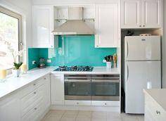 dosseret de cuisine turquoise avec une hotte aspirante et frigo