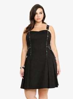 Rocking a cool overall style, this black jumper dress by Tripp NYC features two black faux leather accents that are studded down the front and a removable strap that attaches to them. With a sweetheart neckline and classic overall shoulder straps, the edgy jumper has a pleated skirt and a back zipper entry.