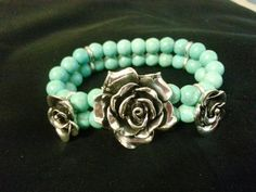 Cowgirl Jewels ... Rosetta ... silver roses is surrounded by two strands of turquoise beads and silver/crystal spacers. Stretch, one size. $10. https://www.facebook.com/RedRiverCowgirlClothingCompany