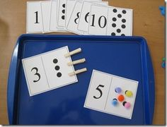 Use clothespins or tweezers with pom poms to put the right number of items on each number card.