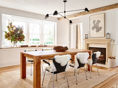 In the dining room in the Hamptons, New York, weekend home of Pilar Guzmán and Chris Mitchell, a Crate and Barrel table is surrounded by vintage Arne Jacobsen chairs draped with sheepskin throws from Design Within Reach  | archdigest.com