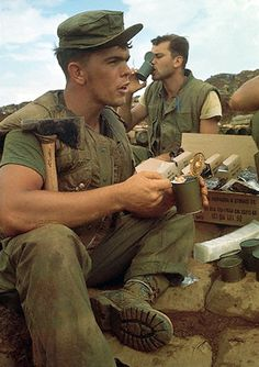 15 Oct 1967, Con Thien, Vietnam --- Picture shows Marines sitting on top of sandbag bunkers take a break to eat beans from a can, October, 15th, at the US Base near the DMZ which is the constrant target for Communist artillery. ~ Vietnam War