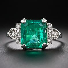 A bright and cheerful, medium green, almost square emerald-cut emerald, of Colombian origin, is presented in classic Art Deco fashion in an architectural platinum and diamond mounting - circa 1930s-40s. The 4.18 carat gemstone is framed left and right with a geometric array of sparkling single-cut diamonds supported by a gracefully flared ring shank.