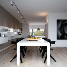 Indulgent grey apartment- modern dining with monochrome setting and rail lighting