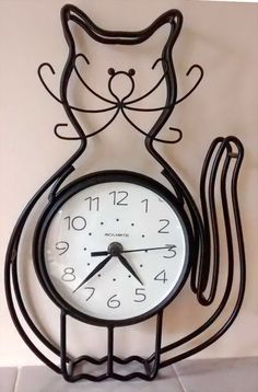 Battery operated clock within black cat metalwork frame. This is a freestanding clock but can also be hung as a wall clock- 33cm high at the tallest point, and 23cm wide at the widest point.