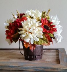 Fall colors, ivory, orange, reds, fall leaves and berries in a rustic bucket. Finished product is 11 tall x 12 wide.