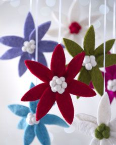 """H6CYR Arcadia Home """"Artisan"""" Clip Christmas Ornaments. Can you believe it -  Horchow sells THESE simple 6 inch diameter flowers in packages of 6 for $100.00! I doubt the exorbitant mark up profit goes to any charity organization.  You could probably make six all by yourself with felt and little white pom poms for $6.00 or less.  They are cute.  Don't try to make them larger than 6 inches in diameter unless you're going to use some super stiff fabric - otherwise the petals will just flop."""