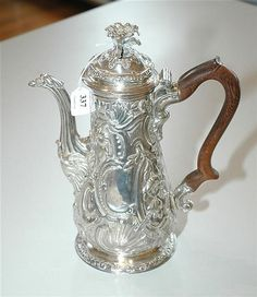 A GEORGE III STERLING SILVER COFFEE POT   Maker's mark rubbed possibly Thomas Heming, London 1754   Baluster, ornately chased with floral and foliate decoration, scroll wooden handle, surmounted by a floral finial, raised on a circular foot.