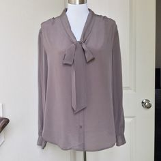 Ann Taylor Blouse This sophisticated blouse includes the following: brownish champagne color, button down with tie around the neck, long sleeves with button at the cuff,  measures 27 inches from shoulder. Brand new with tags. 100% silk. Size L Ann Taylor Tops Blouses