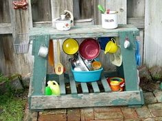 Mudpie kitchen next to the playhouse and sandbox, stocked with thrift store kitchen ware