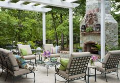 A stone fireplace provides a backdrop for a fall dinner or a few homemade s'mores. To add character, the couple mixed a cherished dining table, which originally belonged to Mark's parents, with new OW Lee patio furniture, pillows and lanterns from Pottery Barn, and a coffee table from Sara Kathryn's, Ltd.