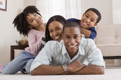 A portrait of a smiling African American family. The father is laying on the carpet of their home, while the mother, young daughter, and then young son pile up on top of him.