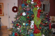 Whoville Christmas  tree Lime green deco mesh with red lots of color. Picks, Sprays,Sprigs, spirals, lots of glitter! Love the snowman and other stuffed items hidden in the tree.