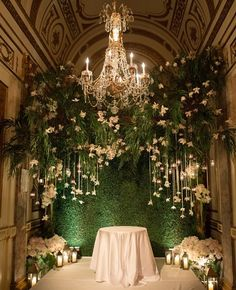 Combine hanging lanterns and flowers with uplighting to create an enchanted garden-inspired wedding altar.