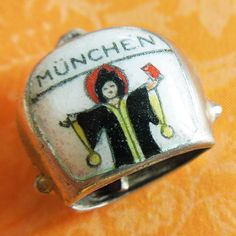 Black line work is transferred then hand-painted onto this traditional-shaped Munchen shield charm representing Munich, Germany. Charm lots of two or more charms will receive one jump ring per lot. Munich, Charms, German, Enamel, Hand Painted, Silver, Vintage, Souvenir, Deutsch