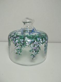 """A hand painted glass cheese cover, or cupcake cover, hand painted in an original My Garden folk art design of daisies and purple cascading hydrangea garden flowers. It was hand painted using acrylic enamel paint. Non-toxic Hand washing recommended. Artist signed. 5.5"""" H, 5"""" across. Lily Of The Valley Flowers, Hand Painted Wine Glasses, Painted Cakes, Altered Bottles, Cake Cover, Scandinavian Art, Arte Popular, Glass Texture, Paint Designs"""