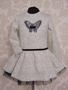 Sukienka Motylek wykonana z dresówki bawełnianej w kolorze szarym. Dół kreacji obszyty czarnym tiulem oraz podszewką. Ozdobiona z przodu czarnym paskiem w pasie. Sukienka posiada długie rękawy oraz kryty zamek.