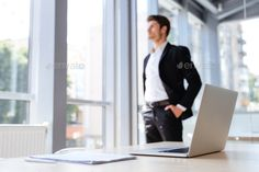Businessman with laptop and documents standing near the window by vadymvdrobot. Handsome young businessman with laptop and documents standing and thinking near the window in office Business Man Photography, Corporate Photography, Male Photography, Photoshop Photography, Business Portrait, Business Photos, African American Men Fashion, Office Pictures, Corporate Headshots