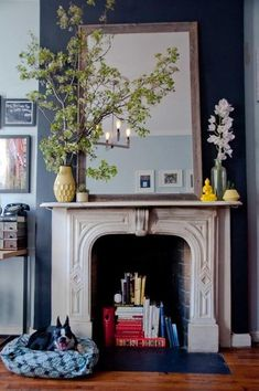 Love this, mirror surrounded by plants and ornaments above fireplace which is being used as a book corner.