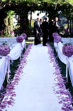 Pomanders of purple roses, scattered petals and purple satin ribbons line the aisle of this outdoor wedding ceremony.