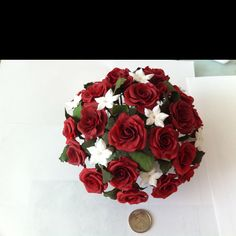 Miniatures red roses and white stephanotis. I created each individual flower using cold porcelain.