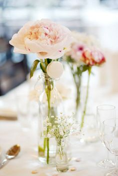 Pink flowers in glass bottles.  Wedding reception centerpieces.