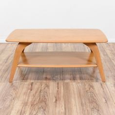 """This """"Heywood Wakefield"""" model #335 coffee table is featured in a solid wood with a gorgeous glossy blonde wood champagne finish. This mid century modern coffee table is in good condition with slanted tapered legs, curved edges and a bottom tier shelf. Stylish and sleek piece! #midcenturymodern #tables #coffeetable #sandiegovintage #vintagefurniture"""
