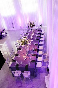 Royal or Captains tables are great for seating large groups at weddings and conserving space. Sheer white ceiling to floor draping creates the romantic balance with the darker purple linens & black napkins (silver chivari chairs).  White and Green centerpieces