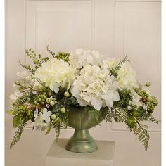 Elegantly styled silk flower centerpiece arranged with white hydrangeas accented with berries, foliage, and fern. Created in an antiqued look green metal bowl.
