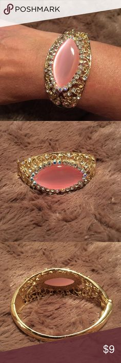 NIB Pink and Goldtone Bangle Bracelet This is a very pretty bangle bracelet still new in the bag.  It has a large pink stone and surrounded by rhinestones in goldtone. Jewelry Bracelets
