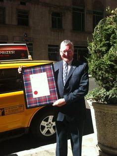 Fergus Ewing prepares to present new tartan to Tartan Parade organisers in NYC.
