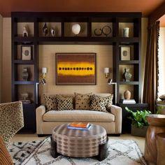 Узкие стеллажи в гостиных ставят и за диванами. Чаще всего этот предмет мебели используется под книги и журналы. Очень удобно, не вставая с дивана, выбирать себе чтение